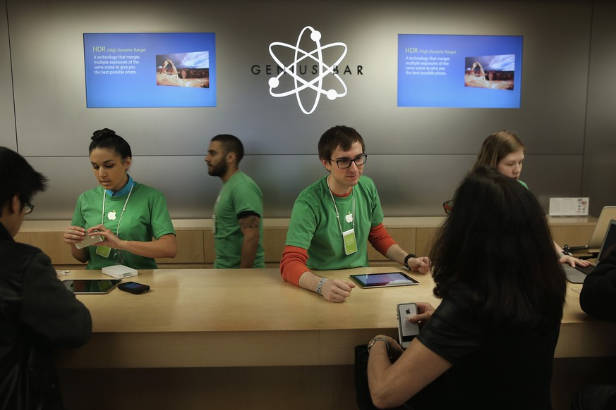 NEW YORK, NY - APRIL 22:  Apple Genius bar employees assist customers at the company's Fifth Avenue store on Earth Day in Midtown Manhattan on April 22, 2014 in New York City. The store is one of at least 120 Apple stores currently powered by renewable energy. To coincide with Earth Day, Apple announced it's offering free recycling of all of its used products. Employees wore green shirts for the occasion.  (Photo by John Moore/Getty Images)