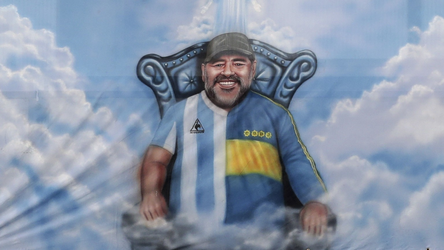 A flag with the image of Diego Maradona wearing the Boca Juniors and Argentine T-shirt hangs from the stands during a local league soccer match between of Boca Juniors and of River Plate at the Bombonera stadium in Buenos Aires, Argentina, Sunday, March 14, 2021.(Alejandro Pagni/Pool via AP)