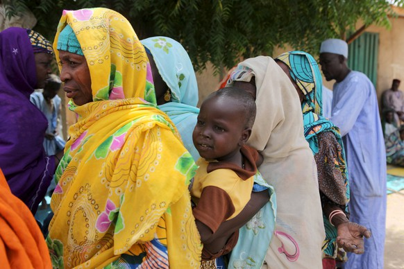 Residents queue for blankets and food distributed by Nigerien soldiers in Damasak March 24, 2015. Boko Haram militants have kidnapped more than 400 women and children from the northern Nigerian town of Damasak that was freed this month by troops from Niger and Chad, residents said on Tuesday. Nigerian, Chadian and Niger forces have driven militants out of a string of towns in simultaneous offensives over the past month.   REUTERS/Joe Penney