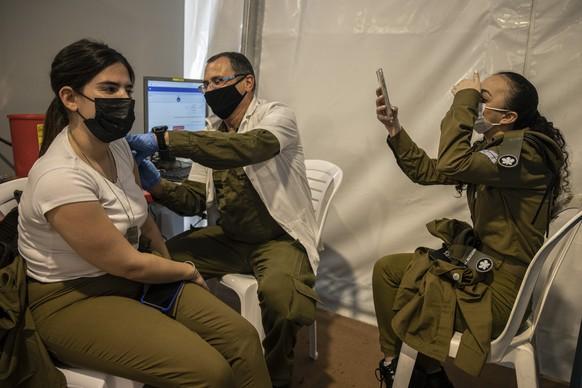 An Israeli soldier receives a Pfizer-BioNTech COVID-19 vaccine, at an Army base, in Rishon Lezion, central Israel, Sunday, Feb. 7, 2021. (AP Photo/Tsafrir Abayov)
