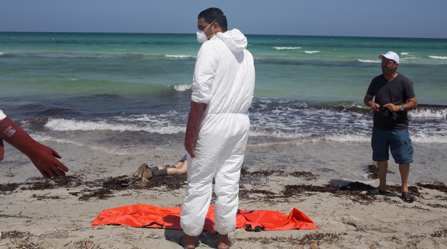 Workers for the Red Crescent pull dead migrants from the water and place them in orange-and-black body bags laid out on the waterfront in Zuwara, about 105 kilometers (65 miles) west of Tripoli, Libya, Friday, Aug. 28, 2015. Two ships went down Thursday off the western Libyan city, where Hussein Asheini of the Red Crescent said over 100 bodies had been recovered. About 100 people were rescued, according to the Office of the U.N. High Commissioner for Refugees, with at least 100 more believed to be missing. (AP Photo/Mohamed Ben Khalifa)