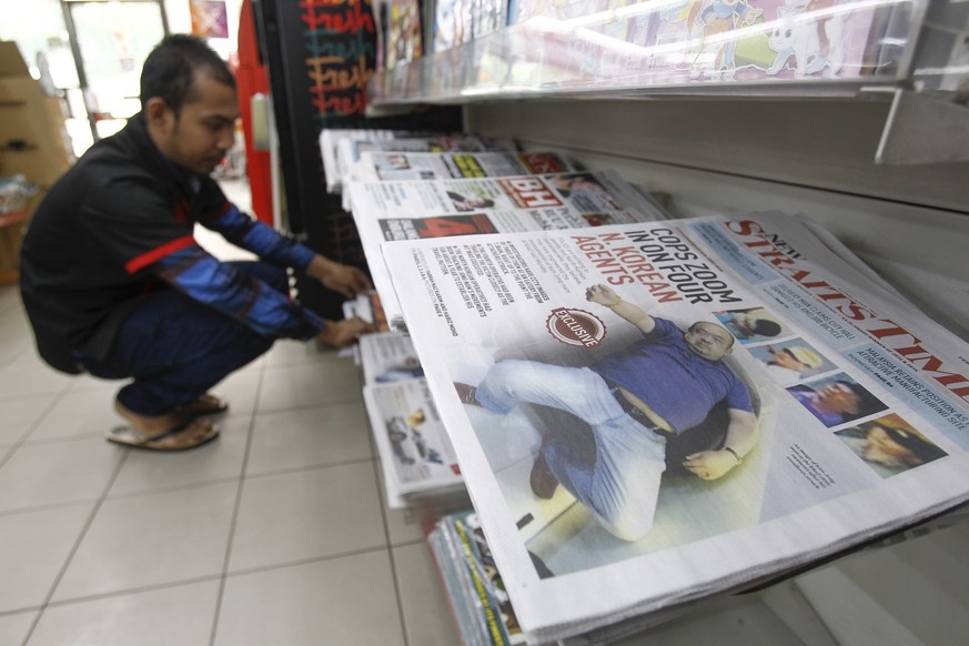 A man arranges the newspaper to the rack inside a mini mart in Kuala Lumpur, Malaysia Saturday, Feb. 18, 2017. North Korea said it will reject the results of an autopsy on its leader's estranged half brother, the victim of an apparent assassination this week at an airport in Malaysia. Pyongyang's ambassador said Malaysian officials may be
