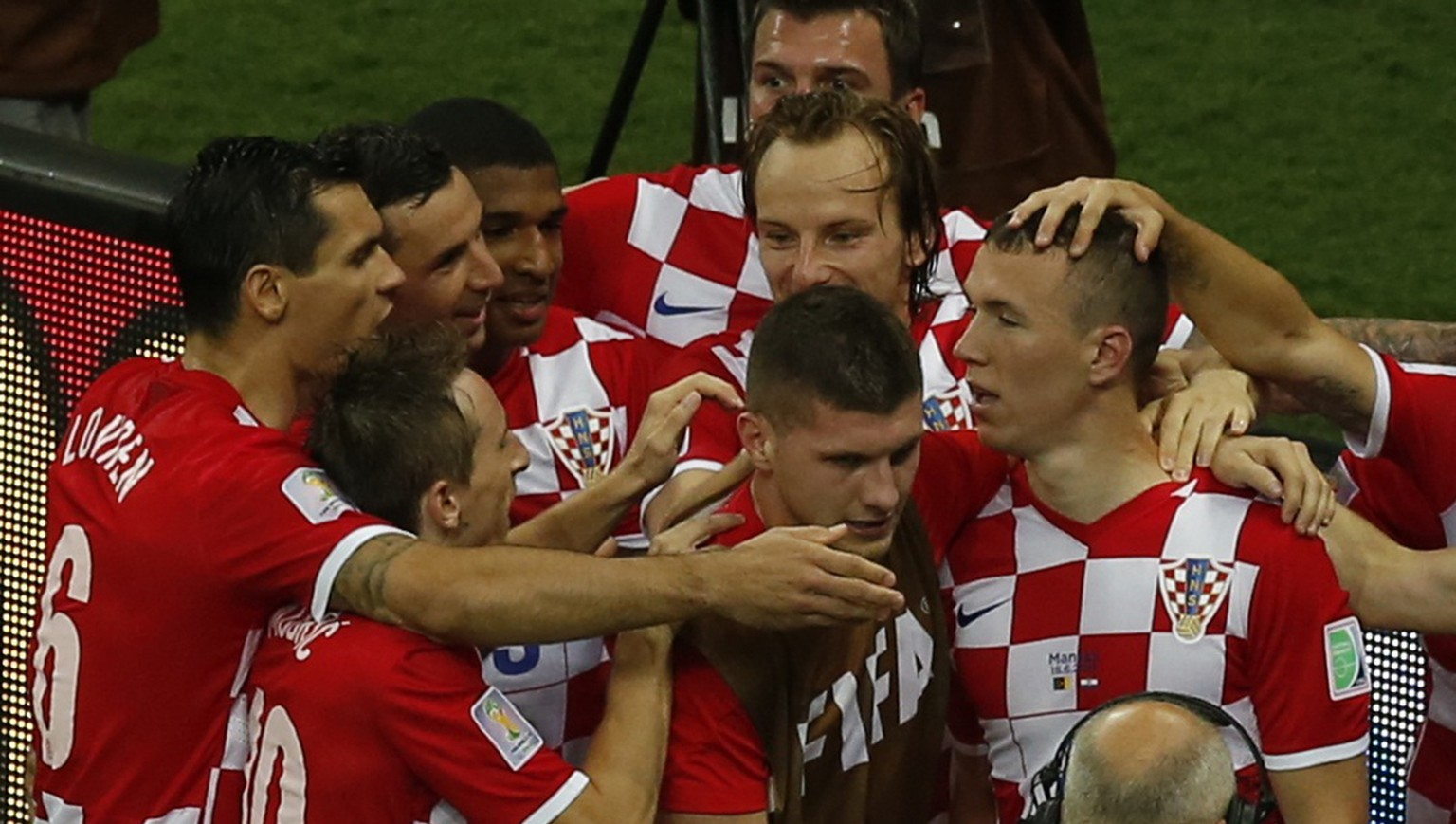 Croatia's Ivan Perisic (R) is hugged by team mates after scoring a goal against Cameroon during their 2014 World Cup Group A soccer match at the Amazonia arena in Manaus June 18, 2014. REUTERS/Andres Stapff (BRAZIL  - Tags: SOCCER SPORT WORLD CUP)