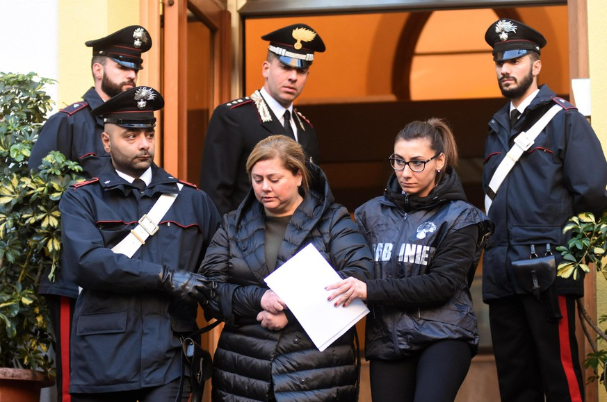 Maria Angela Di Trapani, center, is escorted by Italian Carabinieri, paramilitary Police officers, during an anti Mafia operation which led to the arrest of 25 people, in Palermo, Sicily, Italy, Tuesday, Dec. 5, 2017. According to investigators Di Trapani, the daughter of a mobster and the wife of Mafia boss Salvino Madonia, was at the helm of Palermo's Resuttana Mafia clan. (Mike Palazzotto/ANSA via AP)