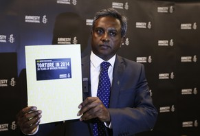 Salil Shetty, Secretary General of Amnesty International, poses for the photographers with a copy of a global report on the use of torture, following its launch in London, Monday, May 12, 2014. According to the organisation, the report exposes how, 30 years on from the introduction of the 1984 Convention Against Torture, more than a hundred states continue to torture – with an range of tools, methods and reasons. (AP Photo/Lefteris Pitarakis)