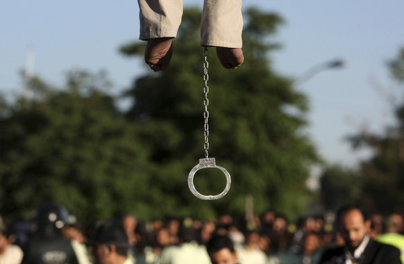 FILE - In this May 26, 2011 file photo, the feet of convicted man Mahdi Faraji, is seen with shackle, while he is being hanged, at the city of Qazvin about 80 miles (130 kilometers) west of the capital Tehran, Iran. Dozens of people who were arrested in Iran for crimes committed before they were 18 remain at risk of the death penalty despite recent reforms, with many having already spent years on death row, according to a report by Amnesty International released Tuesday, Jan. 26, 2016. (AP Photo/Mehr News Agency, Hamideh Shafieeha, File)