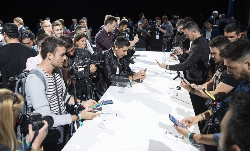epa07853482 People inspect the new Huawei Mate 30 and 30 Pro smartphones after the presentation in Munich, Germany, 19 September 2019.  EPA/LUKAS BARTH-TUTTAS
