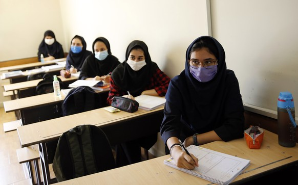 epa08648213 Iranian high school girls wearing face masks attend a class at the Bamdad Parsi private school during the first day of reopening schools, north of Tehran, Iran, 05 September 2020. Media reported that school reopened in Iran during the coronavirus crises in the country.  EPA/ABEDIN TAHERKENAREH