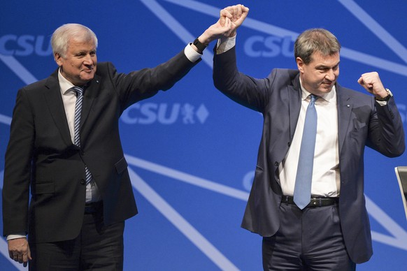 epa06393085 Bavarian Prime Minister and head of the Christian Social Union (CSU) party, Horst Seehofer (L), and Bavarian Finance Minister Markus Soeder of the Christian Social Union (R) demonstrate their soldarity after Soeder's nomination speech during the annual convention of the Christian Social Union party (CSU) in Nuremberg, Germany, 16 December 2017. In their two-day meeting, delegates will vote a new head of party and the top candidate for federal state elections in Bavaria in autumn 2018.  EPA/PHILIPP GUELLAND