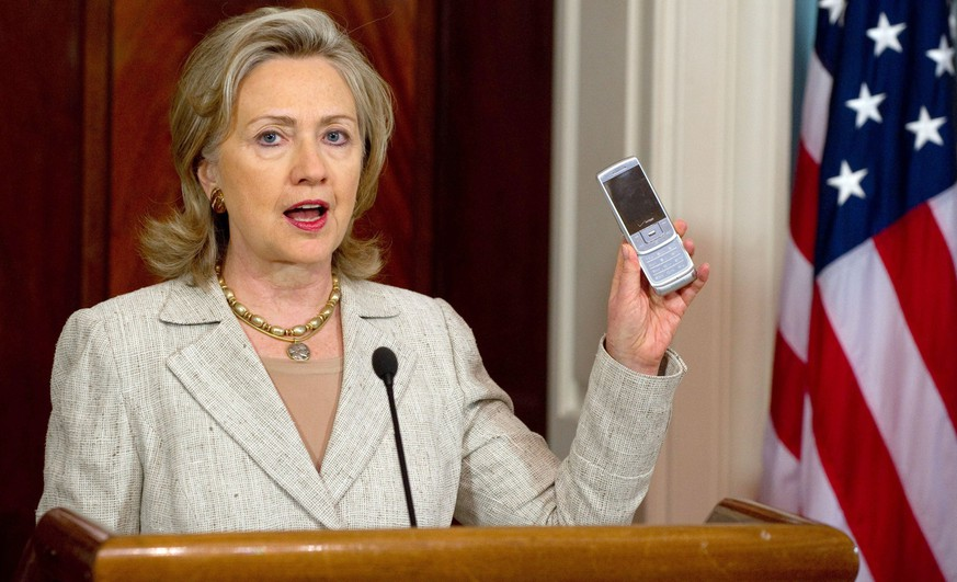 (FILES) - Picture taken August 4, 2010 shows US Secretary of State Hillary Clinton holding up a cell phone as she explains how Americans can donate via text message to aid in helping victims of severe flooding in Pakistan, during a statement at the State Department in Washington, DC.  The German Federal Intelligence Service (BND) intercepted a telephone conversation of the then US Secretary of State, Hillary Clinton according to German newspaper