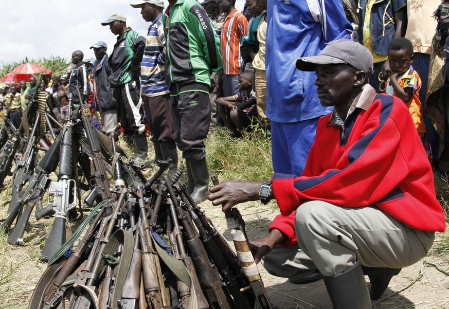 A militant from the Democratic Forces for the Liberation of Rwanda (FDLR) squats near a pile of weapons after their surrender in Kateku, a small town in eastern region of the Democratic Republic of Congo (DRC), May 30, 2014. According to a UN official, 105 militants surrendered and handed their weapons to a United Nations peace keeping force in Kateku. REUTERS/Kenny Katombe (DEMOCRATIC REPUBLIC OF CONGO - Tags: CIVIL UNREST POLITICS MILITARY)
