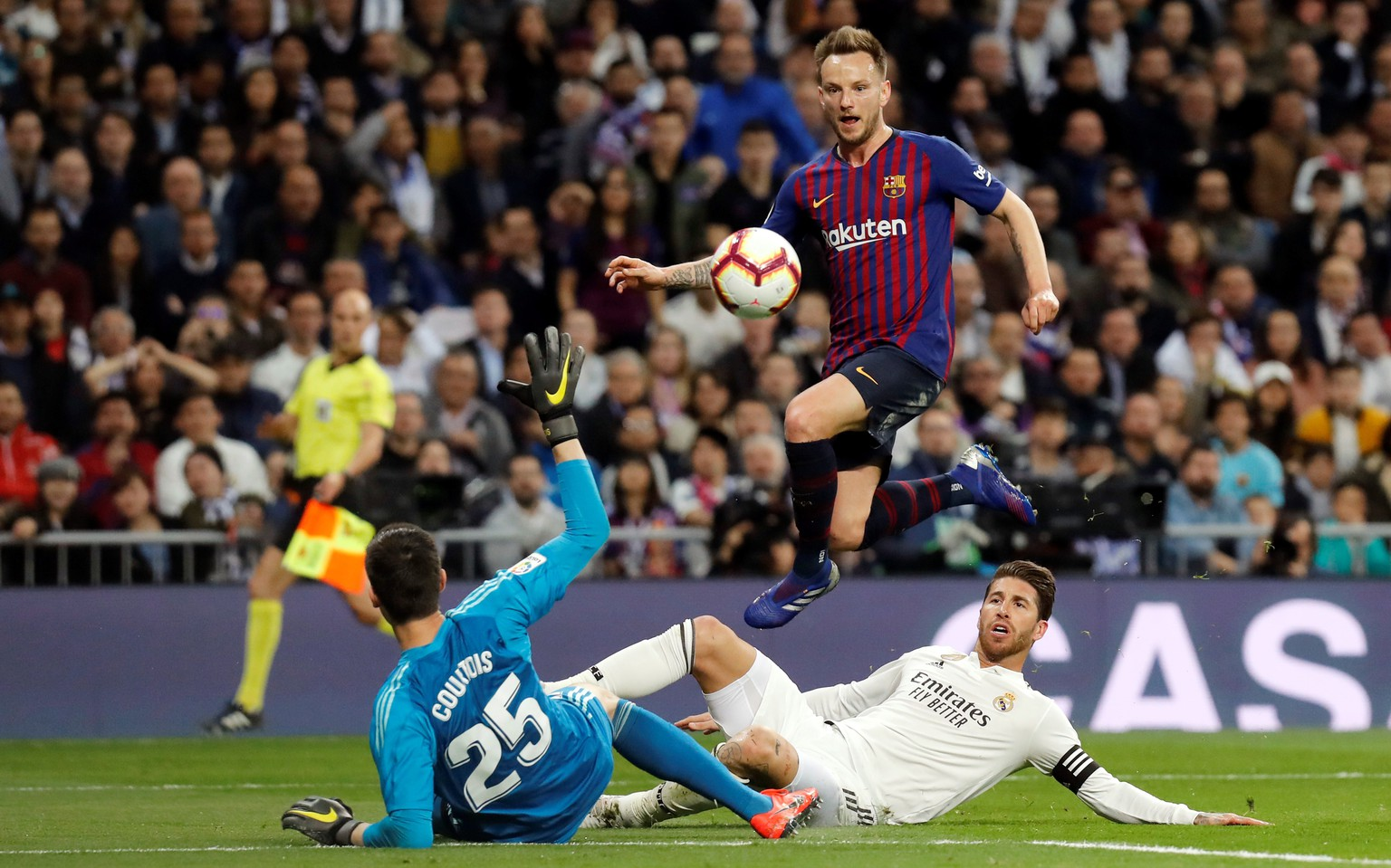 epa07409553 FC Barcelona's Ivan Rakitic (top) beats Real Madrid's goalkeeper Thibaut Courtois (bottom) and Sergio Ramos (R) to score the 0-1 lead during a Spanish LaLiga soccer match between Real Madrid and FC Barcelona at the Santiago Bernabeu stadium in Madrid, Spain, 02 March 2019.  EPA/Juan Carlos Hidalgo
