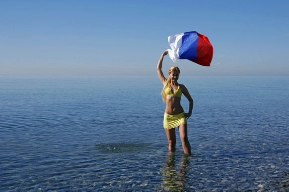 Fashion TV host Lana Prince poses in the water waving the Russian national flag near the Olympic Park on a sunny day at the 2014 Sochi Winter Olympics, February 13, 2014.   REUTERS/Eric Gaillard (RUSSIA  - Tags: OLYMPICS SPORT ENVIRONMENT FASHION MEDIA)