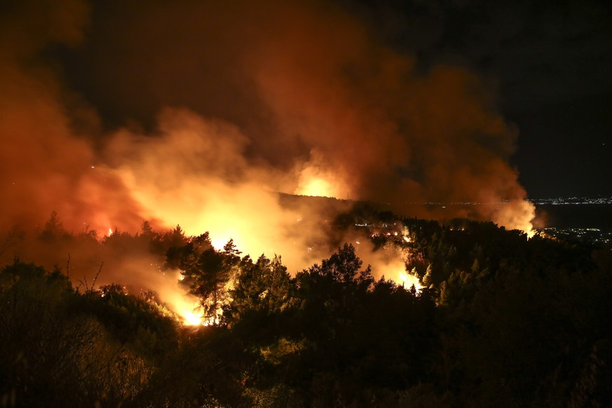 Flames and smoke rise from a forest fire at Kalamos village, north of Athens, on Sunday, Aug. 13, 2017. Fires breaking out across Greece have stretched firefighting capabilities to the limit, authorities say, voicing suspicions that at least some of the fires have been started deliberately. (AP Photo/Yorgos Karahalis)