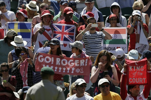 Spectators hold up banners on Centre Court ahead of the  singles first round match between Roger Federer of Switzerland and Damir Dzumhur of Bosnia at the All England Lawn Tennis Championships in Wimbledon, London, Tuesday June 30, 2015. (AP Photo/Tim Ireland)