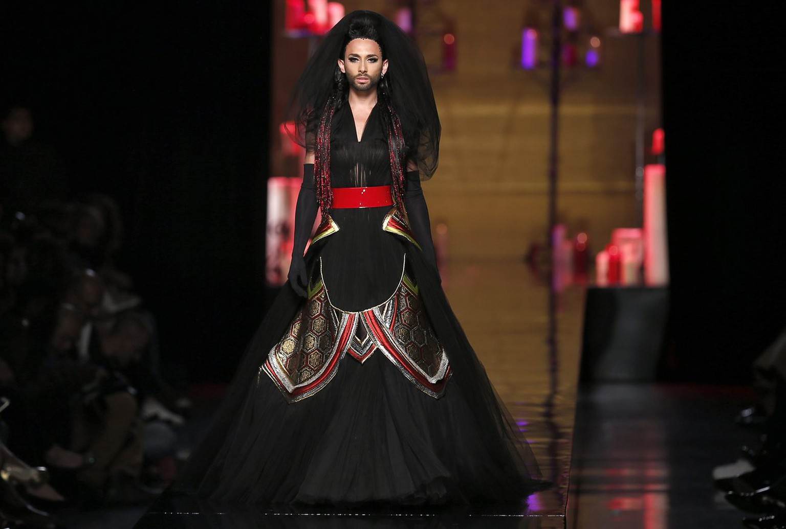 epa04307492 Austrian singer and Eurovision winner Conchita Wurst presents a creation from the Haute Couture Fall-Winter 2014/15 collection by French designer Jean-Paul Gaultier during the Paris Fashion Week, in Paris, France, 09 July 2014. The presentation of the Women's Haute Couture collections runs from 06 to 10 July.  EPA/IAN LANGSDON