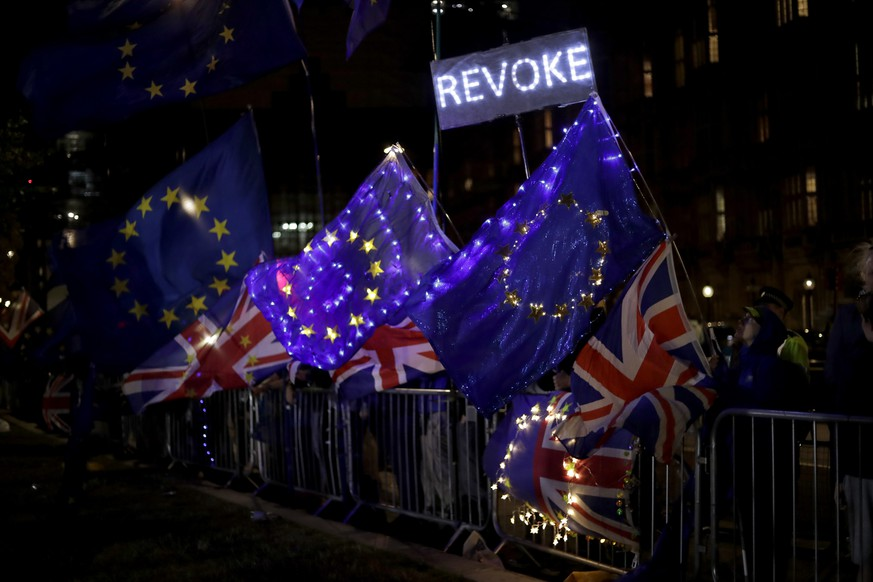 European flags are held by remain in the EU supporters as they demonstrate opposite the Houses of Parliament in London, Wednesday, Sept. 4, 2019. With Britain's prime minister weakened by a major defeat in Parliament, defiant lawmakers were moving Wednesday to bar Boris Johnson from pursuing a