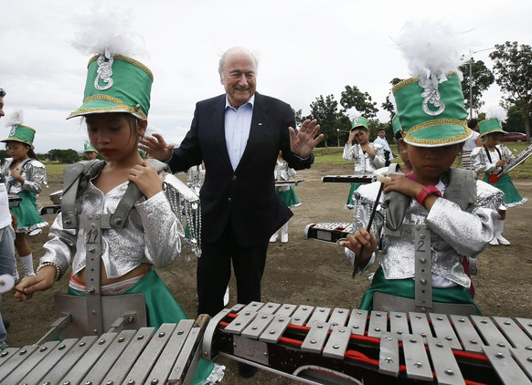 epa04509172 FIFA president Joseph Blatter (C)  greets Filipino students playing percussion instruments following  the Ground Breaking Ceremony of the FIFA Goal Project III for the national teams' training center at the San Lazaro Leisure and Business Park in Carmona, Cavite province, south of Manila, Philippines, 30 November 2014. Blatter is in Manila to attend The Asian Football Confederation (AFC) Annual Awards in conjunction with the AFC's 60th anniversary celebrations. FIFA president Joseph Blatter is seeking to win a fifth term atop FIFA in 2015 following a corruption allegations around the World Cup 2018 and 2022 bidding process.  EPA/DENNIS M. SABANGAN