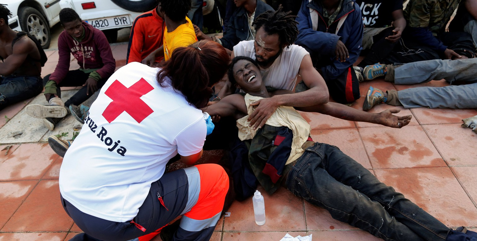 A Spanish Red Cross worker aids African migrants after they crossed a border fence between Morocco and Spain's north African enclave of Ceuta October 31, 2016. REUTERS/M. Martin          FOR EDITORIAL USE ONLY. NO RESALES. NO ARCHIVES.