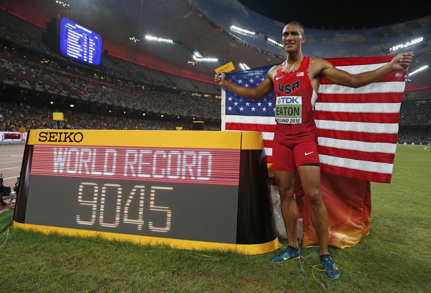 Ashton Eaton of the U.S. poses for photographs after winning the men's decathlon and breaking the world record during the 15th IAAF Championships at the National Stadium in Beijing, China, August 29, 2015.   REUTERS/Phil Noble