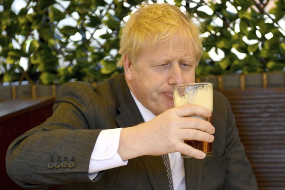 Britain's Prime Minister Boris Johnson sips a pint in the beer garden of The Mount pub and restaurant in Wolverhampton, central England, Monday April 19, 2021, during the Conservative party election campaign. (Jacob King/Pool via AP)