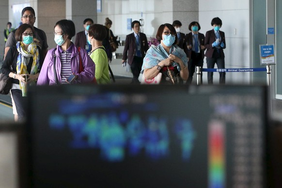 Passengers wearing masks to prevent contracting Middle East Respiratory Syndrome (MERS) walk past a thermal imaging camera at Incheon International Airport in Incheon, South Korea, June 1, 2015. South Korea struggled to contain an outbreak of Middle East Respiratory Syndrome (MERS) on Monday as health authorities announced three more cases, bringing the number of infections to 18 in just over 10 days.  REUTERS/Kim Ju-sung/Yonhap  ATTENTION EDITORS - NO SALES. NO ARCHIVES. FOR EDITORIAL USE ONLY. NOT FOR SALE FOR MARKETING OR ADVERTISING CAMPAIGNS. THIS IMAGE HAS BEEN SUPPLIED BY A THIRD PARTY. IT IS DISTRIBUTED, EXACTLY AS RECEIVED BY REUTERS, AS A SERVICE TO CLIENTS. SOUTH KOREA OUT. NO COMMERCIAL OR EDITORIAL SALES IN SOUTH KOREA