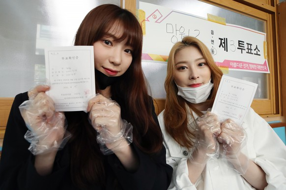 epa08363360 Soo Yoon (L) and Yoon Kyung (R), members of South Korean girl group Rocket Punch, pose for a photo after casting their ballots for the general elections at a polling station in Seoul, South Korea, 15 April 2020. The election for a 300-seat unicameral National Assembly is widely seen as a referendum on President Moon Jae-in amid the country's fight against the coronavirus pandemic.  EPA/YONHAP SOUTH KOREA OUT