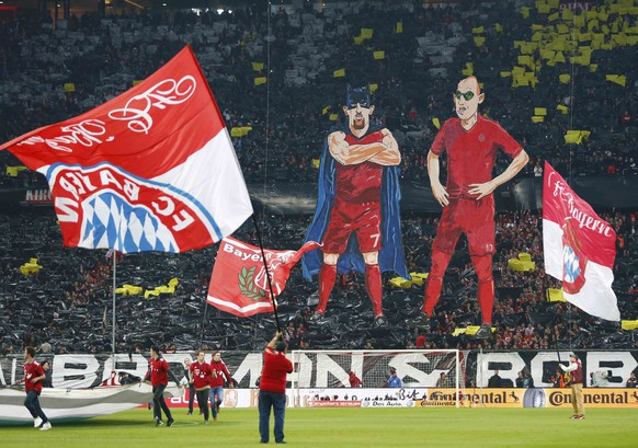 Bayern Munich fans display a large banner with caricatures of players Franck Ribery (L) and Arjen Robben (R) as super heroes 'Batman and Ronin' prior to their German Cup (DFB Pokal) semi-final soccer match against Borussia Dortmund in Munich, Germany April 28, 2015.    REUTERS/Michael Dalder  DFB RULES PROHIBIT USE IN MMS SERVICES VIA HANDHELD DEVICES UNTIL TWO HOURS AFTER A MATCH AND ANY USAGE ON INTERNET OR ONLINE MEDIA SIMULATING VIDEO FOOTAGE DURING THE MATCH.