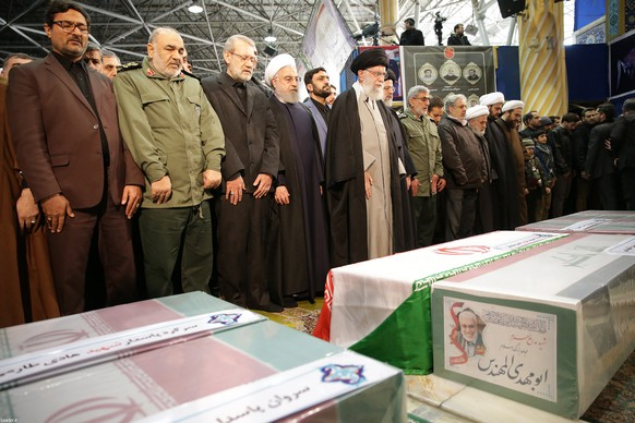 epa08107271 A handout photo made available by Iranian Supreme Leader's Office shows Iranian Supreme Leader Ayatollah Ali Khamenei (C) praying before the coffins of slain Iranian Revolutionary Guards Corps (IRGC) Lieutenant general and commander of the Quds Force Qasem Soleimani and of other victims as Iranian President Hassan Rouhani (C-L) and other top officials attend the funeral ceremony in Tehran, Iran, 06 January 2020. Soleimani was killed in a targeted US airstrike on 03 January 2020 in Baghdad, Iraq.  EPA/IRAN'S SUPREME LEADER OFFICE HANDOUT  HANDOUT EDITORIAL USE ONLY/NO SALES