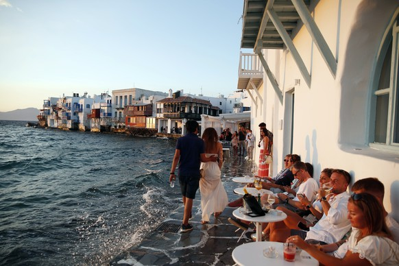 People sit at a bar in Little Venice on the Aegean Sea island of Mykonos, Greece, Sunday, Aug. 16, 2020. Wary of a rise in daily coronavirus cases that threatens to undo its relative success in containing the pandemic so far, the Greek government is imposing local restrictions on businesses, especially those that cater to big crowds, and business owners on the island of Mykonos don't like it one bit. (AP Photo/Thanassis Stavrakis)