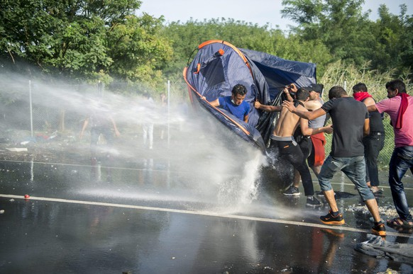 epa04933528 Hungarian police use water canons against demonstratring migrants at the border crossing into Hungary, near Horgos, Serbia, 16 September 2015. The border crossing was closed by the Hungarian police after the Hungarian government declared a state of crisis due to mass migration, meaning special measures to fight illegal immigration, in two Hungarian countries bordering Serbia.  EPA/TAMAS SOKI HUNGARY OUT