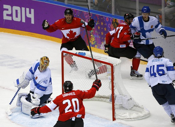 Canada's Drew Doughty (8) celebrates teammates John Tavares and Jeff Carter (77) after scoring the game-winning overtime goal against Finland's goalie Tuukka Rask in their men's preliminary round ice hockey game at the 2014 Sochi Winter Olympics, February 16, 2014.        REUTERS/Brian Snyder (RUSSIA  - Tags: OLYMPICS SPORT ICE HOCKEY TPX IMAGES OF THE DAY)