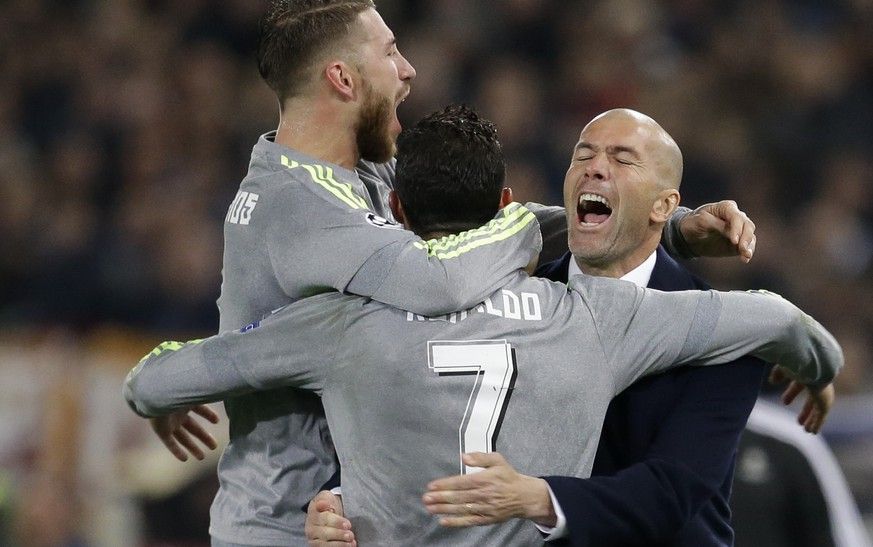 Real Madrid's Cristiano Ronaldo, center, celebrates with teammate Sergio Ramos and coach Zinedine Zidane after scoring, during a Champions League, round of 16, first-leg soccer match between Roma and Real Madrid, at the Rome Olympic stadium, Wednesday, Feb. 17, 2016. (AP Photo/Andrew Medichini)