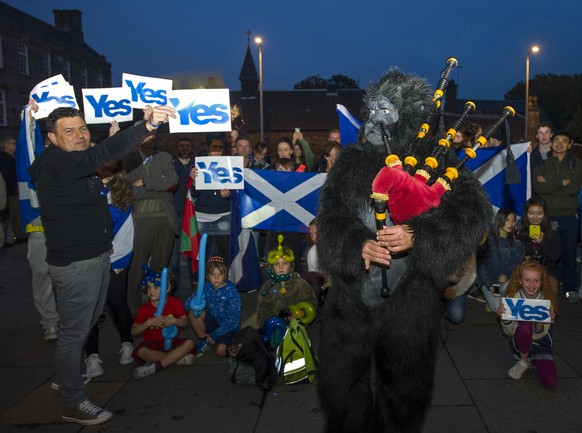 Pro-Independence, 'Yes' supporters are entertained by a piper dressed as a gorilla outside the Scottish Parliament in Edinburgh on September 18, 2014, during Scotland's independence referendum. Scotland voted Thursday in an epic independence referendum that could break up the centuries-old United Kingdom and create Europe's newest state since the collapse of Yugoslavia. AFP PHOTO/LESLEY MARTIN