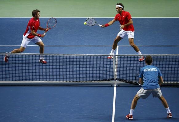 Switzerland's Stanislas Wawrinka (L) and Roger Federer (C) play a ball during their Davis Cup quarter-final tennis match against Andrey Golubev and Aleksandr Nedovyvesov of Kazakhstan in Geneva April 5, 2014.  REUTERS/Denis Balibouse (SWITZERLAND  - Tags: SPORT TENNIS)