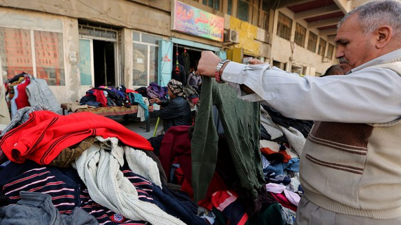 epa05653575 An Iraqi vendor displays used clothes for sale at his shop in central Baghdad, Iraq, 30 November 2016. Scores of shops are selling used clothes at low prices for the poor and low-income people in Baghdad.  EPA/ALI ABBAS