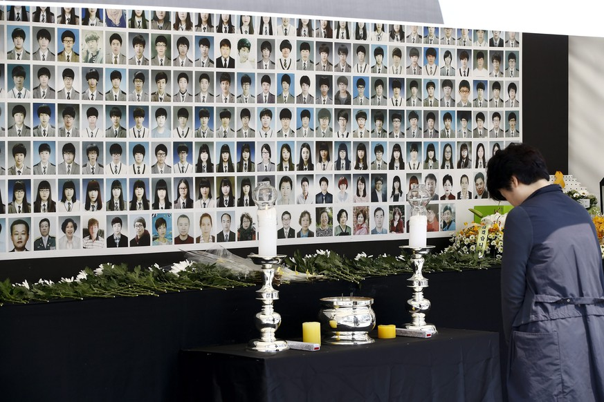 epa04715510 A mourner pays tribute to victims of the Sewol ferry accident at the memorial altar on Gwanghwamun square in Seoul, South Korea, 22 April 2015.  Government announced for ship salvage of Sewol ferry on 22 April. The Sewol ferry sank on 16 April 2014 off the coast of South Korea while carrying 476 people on board. Many of the dead were students on an excursion aboard the overloaded vessel. Of the 476 on board, just 172 survived, including senior crew members who were among the first to leave the stricken ferry. Nine people were declared missing.  EPA/JEON HEON-KYUN