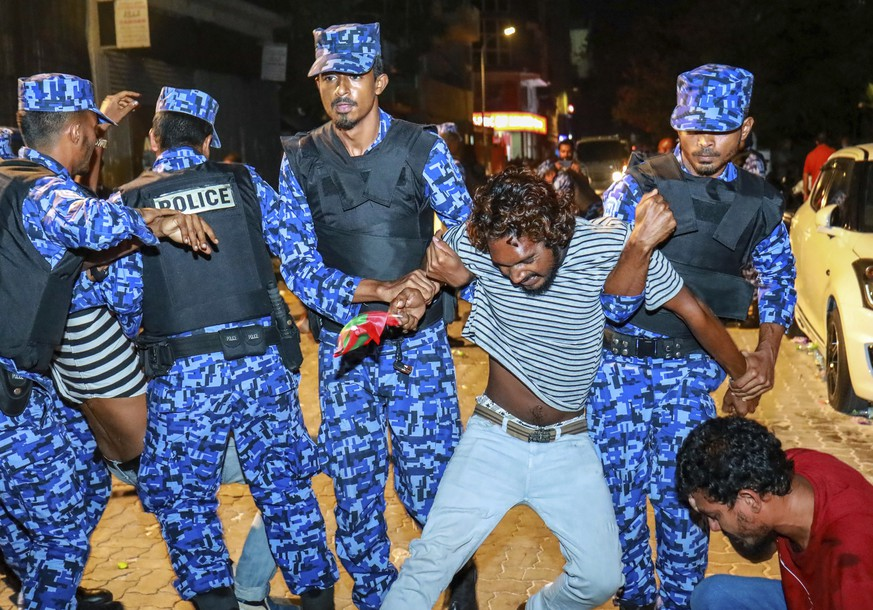 Maldivian police officers detain an opposition protestor demanding the release of political prisoners during a protest in Male, Maldives, Friday, Feb. 2, 2018. Opponents of the Maldives government clashed with police on the streets of the capital Friday as they demanded the release of imprisoned politicians whose convictions were overturned by the Supreme Court.(AP Photo/Mohamed Sharuhaan)