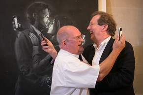 BRISTOL, ENGLAND - AUGUST 27:  Denis Stinchcombe, manager of Broad Plain Boys' Club (L) and Bristol Mayor George Ferguson (R) recreate the image on Banksy's mural 'Mobile Lovers' displayed behind them at Bristol Museum & Art Gallery as it was announced that the art piece by the Bristol underground guerilla artist had sold for £403,000 to a private collector on August 27, 2014 in Bristol, England. The proceeds of the sale, said to have been by a philanthropic private individual, will be shared by the cash-strapped boys' club with other youth projects in the city. There was initially controversy when the club removed the work from a wall nearby, until the artist himself backed its ownership.  (Photo by Matt Cardy/Getty Images)