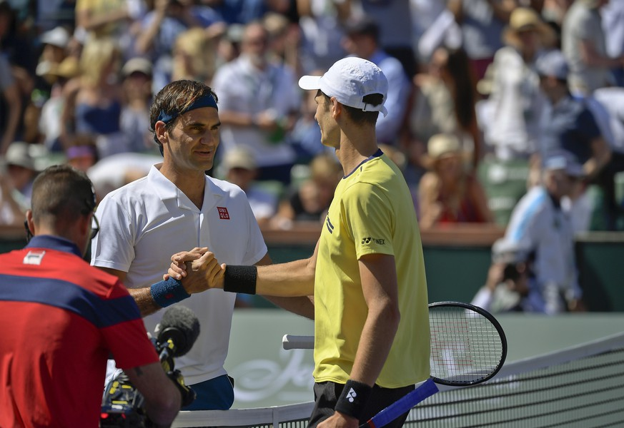 Roger Federer, of Switzerland, left, shakes hands with Hubert Hurkacz, of Poland at the BNP Paribas Open tennis tournament Friday, March 15, 2019, in Indian Wells, Calif. Federer defeated Hurkacz, 6-4, 6-4. (AP Photo/Mark J. Terrill)
