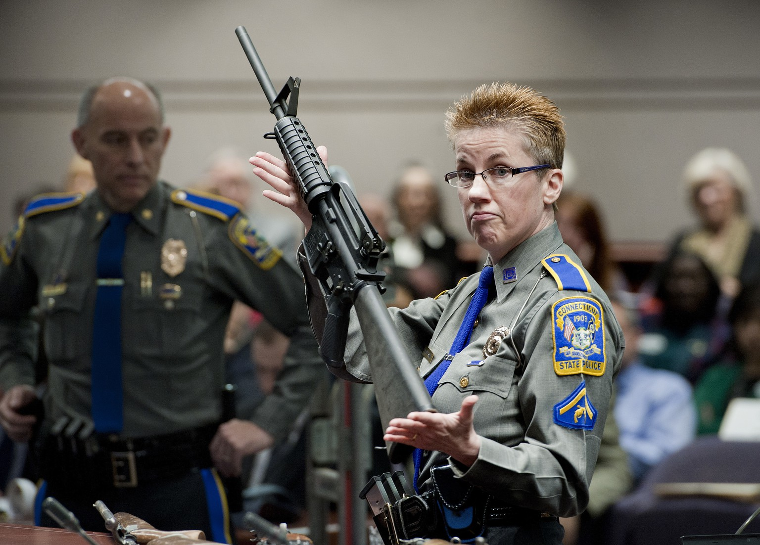 FILE - In this Jan. 28, 2013, file photo, firearms training unit Detective Barbara J. Mattson, of the Connecticut State Police, holds up a Bushmaster AR-15 rifle, the same make and model of gun used by Adam Lanza in the Sandy Hook School shooting, for a demonstration during a hearing of a legislative subcommittee reviewing gun laws, at the Legislative Office Building in Hartford, Conn. Mass shooters have sometimes obtained guns by exploiting limited weapons laws and blind spots in the background-check process or weapons purchased by others. Lanza used his mother's weapons in the massacre at Sandy Hook Elementary School. (AP Photo/Jessica Hill, File)