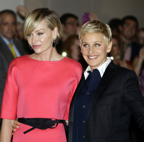 Entertainer Ellen DeGeneres, right, with her wife Portia de Rossi, pose for photographers on the red carpet before DeGeneres receives the 15th annual Mark Twain Prize for American Humor at the Kennedy Center, Monday, Oct. 22, 2012, in Washington. (AP Photo/Alex Brandon)