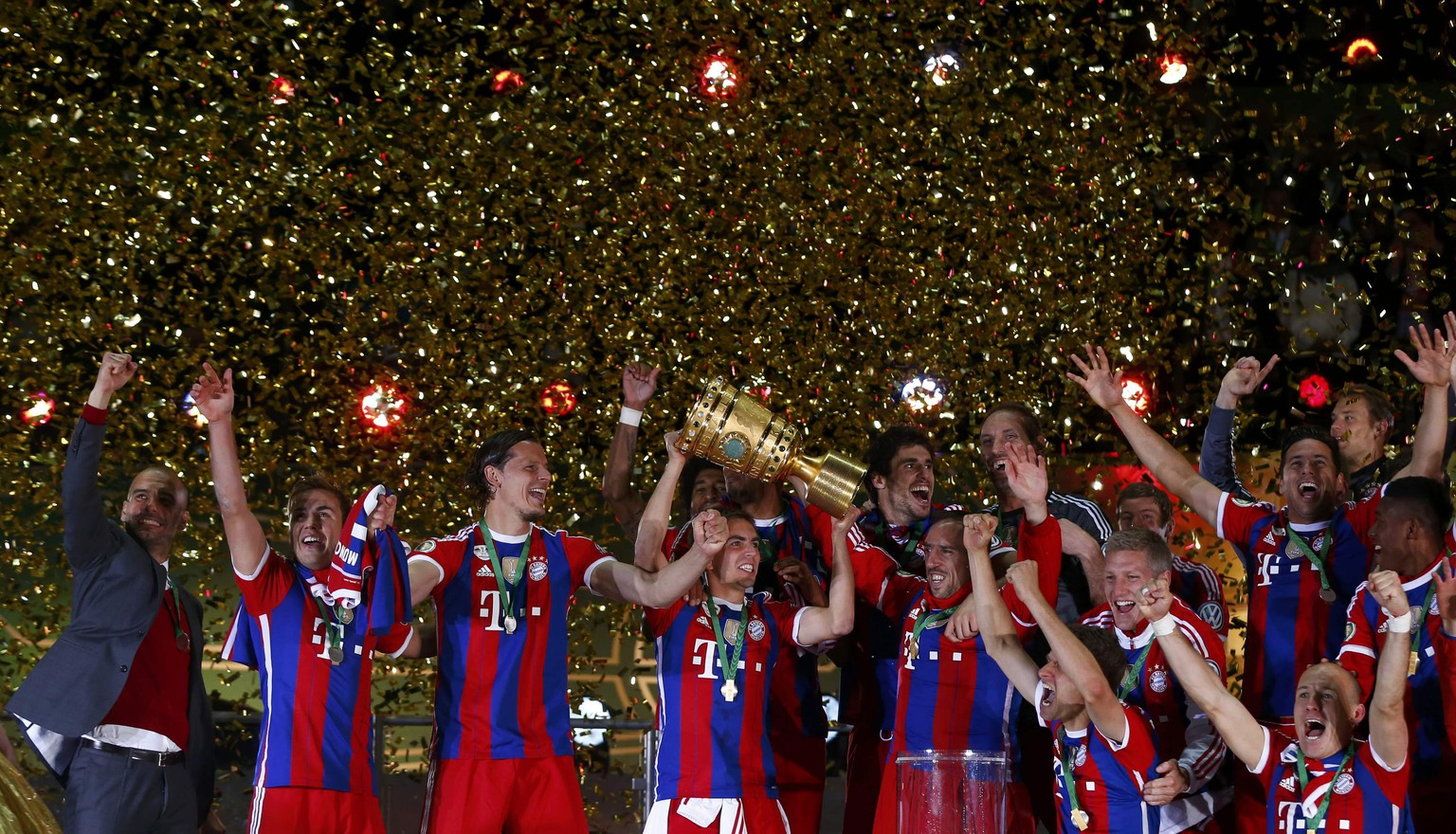 Bayern Munich's captain Philipp Lahm lifts up the trophy as the team celebrates after their German Cup (DFB Pokal) final soccer match against Borussia Dortmund in Berlin May 17, 2014.   REUTERS/Michael Dalder (GERMANY  - Tags: SPORT SOCCER) DFB RULES PROHIBIT USE IN MMS SERVICES VIA HANDHELD DEVICES UNTIL TWO HOURS AFTER A MATCH AND ANY USAGE ON INTERNET OR ONLINE MEDIA SIMULATING VIDEO FOOTAGE DURING THE MATCH.