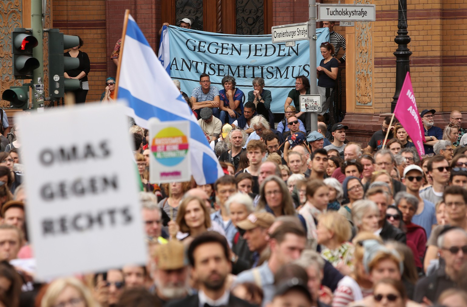 epa07917946 Protesters attend a demonstration against antisemitism and racism held outside the Neue Synagoge, or New Synagogue (unseen), in Berlin, Germany, 13 October 2019. Organized by the 'Unteilbar' solidarity with minorities protests, the demonstration was held four days after a racist and antisemitic attack in the East German city of Halle killed two people.  EPA/ADAM BERRY