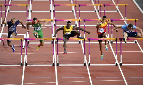 Jamaica's Omar McLeod, centre, jumps the final hurdle on his way to winning the Men's 110 meters hurdles final at the World Athletics Championships in London Monday, Aug. 7, 2017. (AP Photo/Martin Meissner)