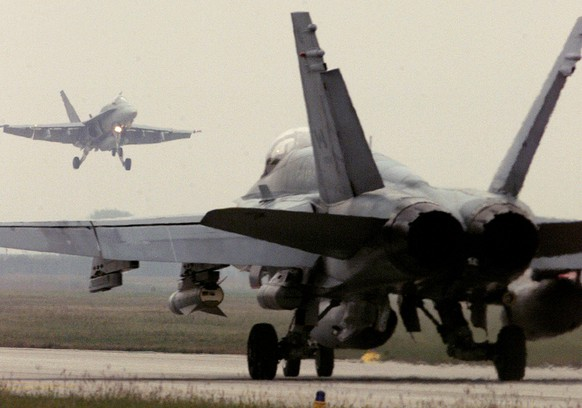 A Canadian F-18 Hornet fighter jet lands while another prepares to take off  from the Italian-American NATO air base in Aviano in this October 12, 1998 file photo. Canadian fighter jets have made their first combat strike since joining the campaign against Islamic State fighters in Iraq on Oct. 30, 2014,  Canada's Defense Minister said on Sunday.   REUTERS/Vincenzo Pinto/Files    (IRAQ - Tags: CONFLICT POLITICS)