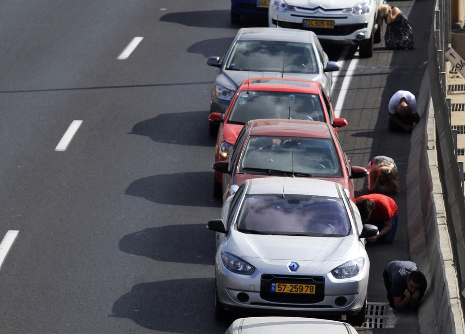 Drivers take cover beside their cars on a highway as an air raid siren, warning of incoming rockets, sounds in Tel Aviv July 9, 2014. Israeli air strikes shook Gaza every few minutes on Wednesday, and militants kept up rocket fire at Israel's heartland in intensifying warfare that Palestinian officials said has killed at least 47 people in the Hamas-dominated enclave. REUTERS/Stringer (ISRAEL - Tags: POLITICS CIVIL UNREST)