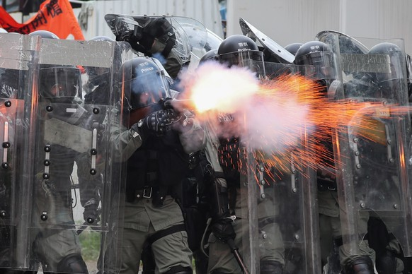 epa07891105 Riot police fire tear gas during a mass rally in Yuen Long, New Territories, Hong Kong, China, 27 July 2019. Anti-extradition bill protesters took to the streets to denounce the break out of violence on 21 July when more than 100 white-clad men suspected of being triads members beat up travellers in the Yuen Long MTR station. Some of whose victims had come from a march against the government?s now-suspended extradition bill.  EPA/RITCHIE B. TONGO
