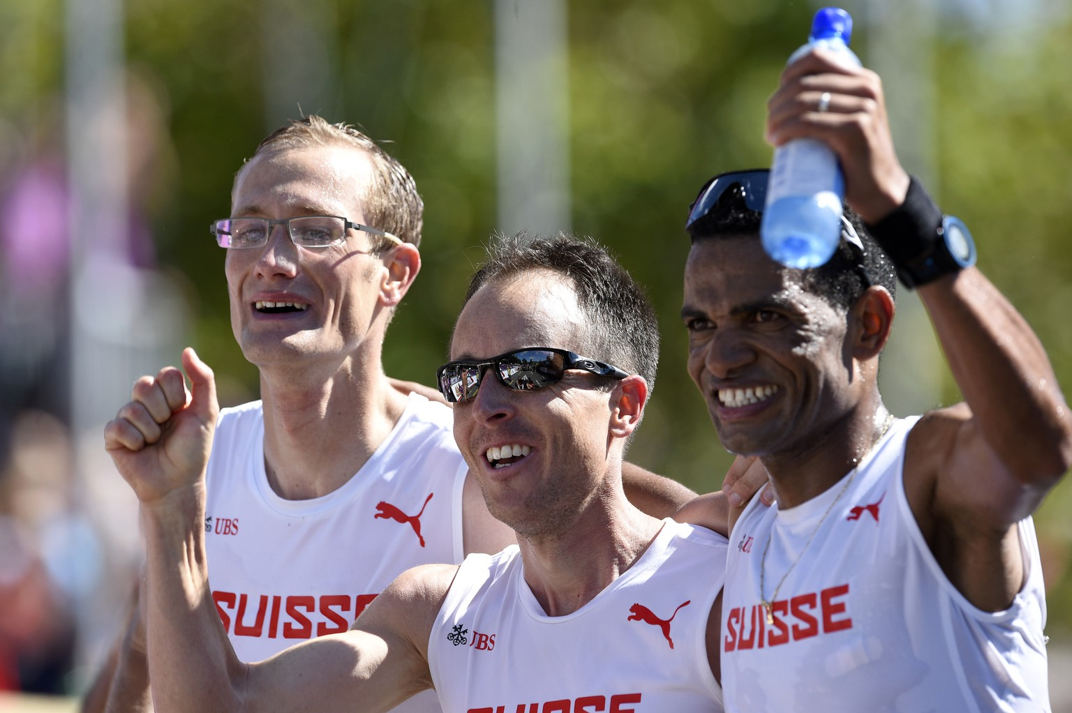Switzerland's Christian Kreienbuehl, Viktor Roethlin and Tadesse Abraham, from left to right, cheers, after winning the team event gold in the men's Marathon in the city centre of Zurich, at the sixth day of the European Athletics Championships in the Letzigrund Stadium in Zurich, Switzerland, Sunday, August 17, 2014. (KEYSTONE/Ennio Leanza)