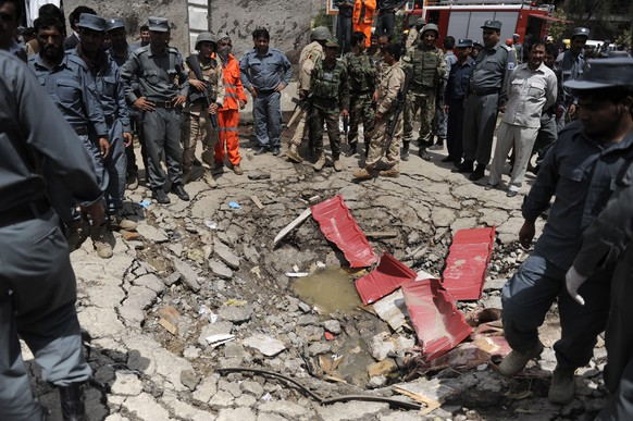 epa04813704 Afghan security officials stand beside a crater that was formed at the scene of a suicide bomb attack outside  the Afghan Parliament, in Kabul, Afghanistan, 22 June 2015. Several explosions rocked the Afghanistan Parliament on 22 June when newly nominated Afghan Defence Minister Masoom Stanekzai was due to secure a vote of confidence for his new position.  EPA/JAWAD JALALI